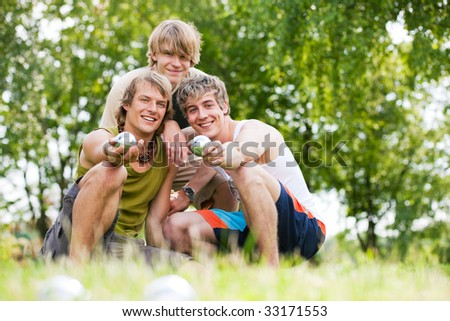 Group of young men playing boule in a park - stock photo