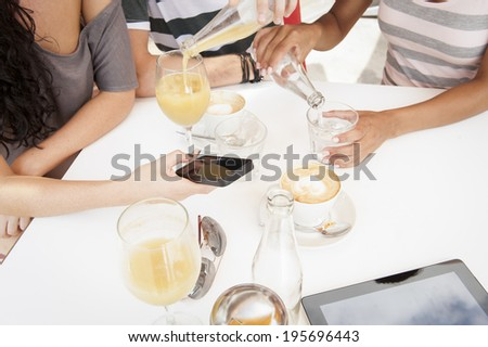 group of young mixed race people socializing at coffee shop - stock photo