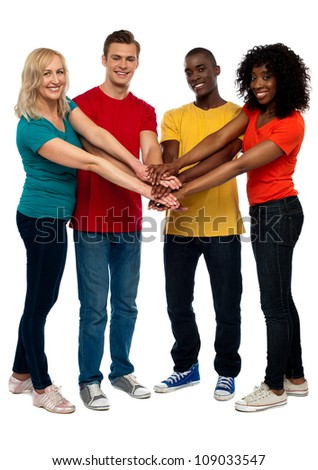 Group of young multicultural friends posing with hands on hands looking at you - stock photo