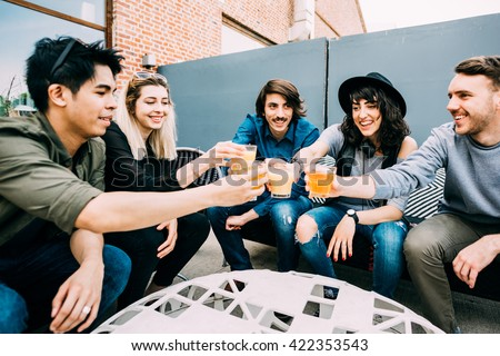 Group of young multiethnic friends sitting in a bar toasting, talking to each other, having fun - happy hour, friendship, relax concept - stock photo
