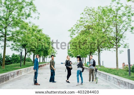 Group of young multiethnic friends standing outdoor ina city park, turning looking in camera, holding bike and skate, smiling - happiness, friendship concept - copy space on top - stock photo