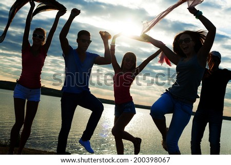 group of young people dancing at a beach party at sunset - stock photo