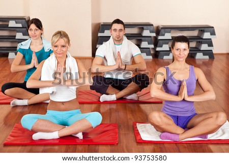 Group of young people doing yoga exercises - stock photo