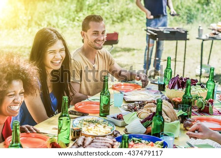 Group of young people enjoying park outdoor barbecue - Multi ethnic cheerful friends eating and drinking together - Summer meal and party concept - Focus on white girl - Desaturated vintage filter - stock photo