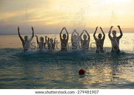 group of young people fun on the beach , making fun and playing in water, jumping out of water on sandy beach,  fashion photo of group of young people playing in water on summer beach in sunlight rays - stock photo