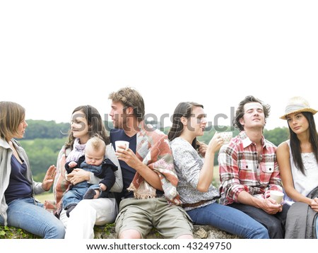 Group of young people having coffee outside in the morning, with one woman holding a baby. Horizontal. - stock photo