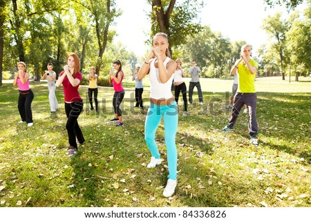 group of young people having kick boxing training , outdoor - stock photo