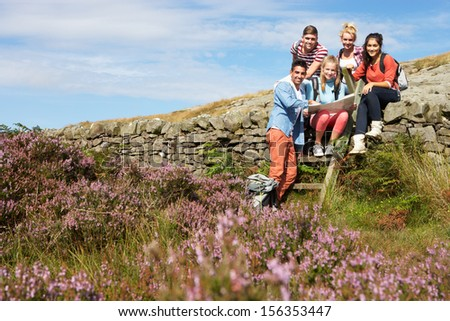 Group Of Young People Hiking Through Countryside - stock photo
