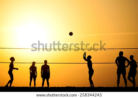 group of young people igoat in volleyball on the sea coast - stock photo