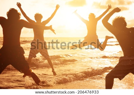 group of young people jumping on the beach with sunset background - stock photo