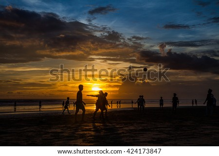 Group of young people playing football on the tropical beach on the Sunset / young people playing football on the tropical beach / Seminyak beach, Bali, Indonesia. - stock photo