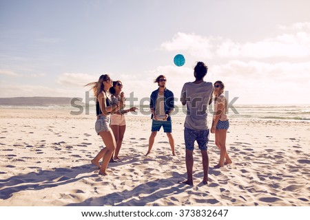 Group of young people playing with ball at the beach. Young friends enjoying summer holidays on a sandy beach. - stock photo