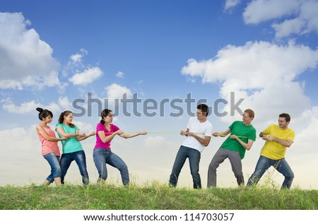 Group of young people pulling a rope, competing outdoors - stock photo