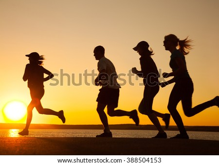 group of young people runs at the beach on beautiful summer sunset - stock photo