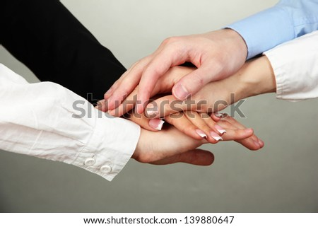 Group of young people's hands on gray background - stock photo
