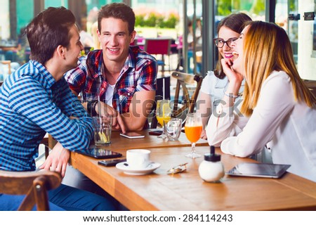 Group of young people sitting at a cafe, talking and enjoying - stock photo