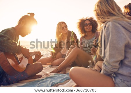 Group of young people sitting at the beach together while young man playing guitar. Group of friends partying on the beach at sunset. - stock photo