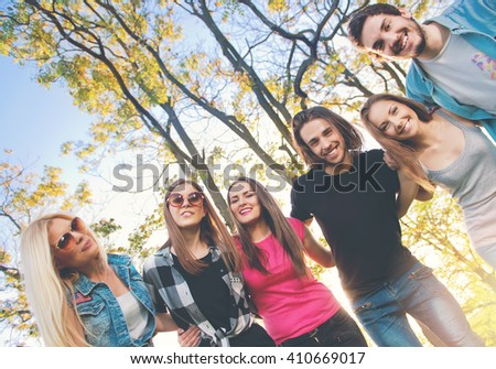 Group of young people standing in a circle, outdoors, having fun  - stock photo