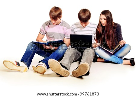 Group of young people studing with books and  laptop. Isolated over white background. - stock photo