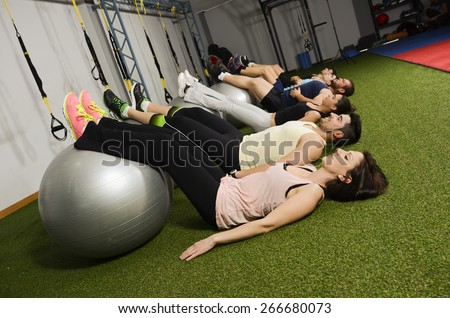Group of young people training with balloon abdominal muscle - stock photo