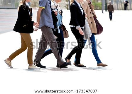 Group of young people walking. Urban scene. - stock photo