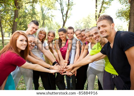 group of young people with their hands together outdoor - stock photo