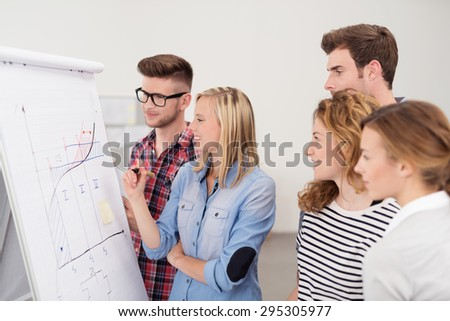 Group of Young Professional People Looking at the Conceptual Graph on Poster Paper Closely Inside the Office. - stock photo