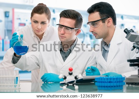 Group of young scientists experimentation in research laboratory - stock photo