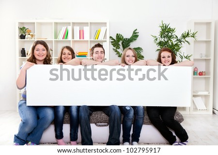 Group of  young smiling teenager holding blank banner in front of them - stock photo