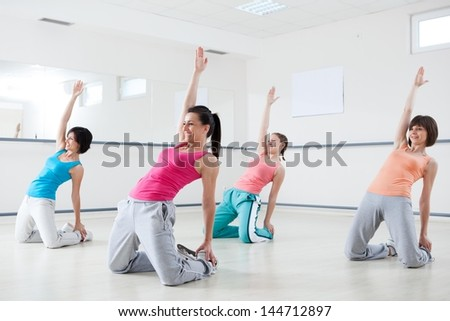 Group of young smiling women doing exercise on aerobic class at a fitness studio. - stock photo