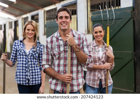 group of young stable workers with tools - stock photo