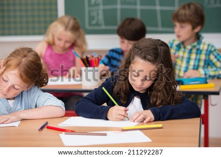 Group of young students in school with focus to a pretty young girl in the front row working on her class notes - stock photo