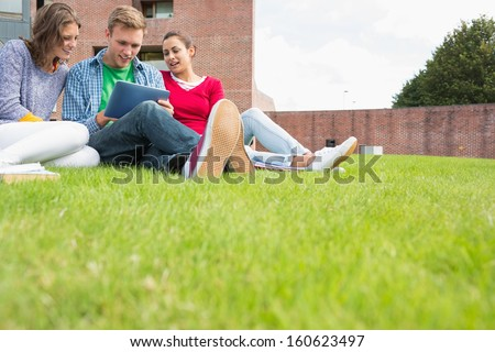 Group of young students using tablet PC in the lawn against college building - stock photo