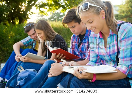 group of young students with books and gadgets sit on the steps in the park - stock photo