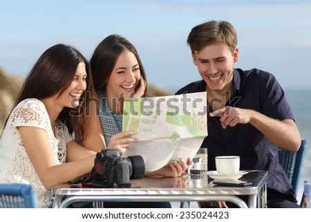 Group of young tourist friends consulting a paper map in a restaurant with the beach in the background - stock photo
