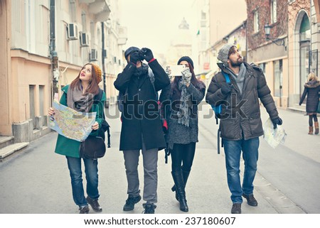 Group Of Young Tourists Enjoying The Cold Weather And Sightseeing City - stock photo