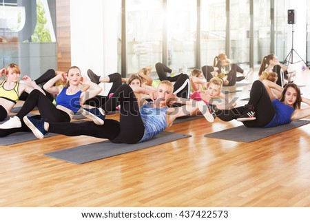 Group of young women in fitness class. Group of people making exercises. Girls do cross crunches for abs. Healthy lifestyle, training, sport, gym studio. Sporty girls in fitness club, aerobics. - stock photo