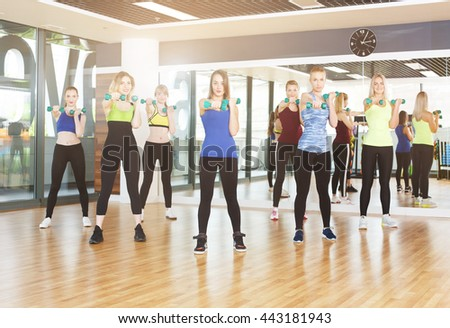 Group of young women in fitness club making exercises with dumbbels. Healthy lifestyle, slim sporty girls at aerobics training. - stock photo