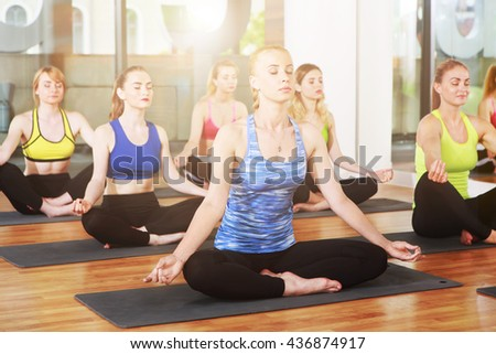 Group of young women in yoga class. Group of people making exercises. Girls do yoga meditation pose, relaxation. Meditation posture. Healthy lifestyle, sport, yoga studio. Fitness club, yoga training - stock photo