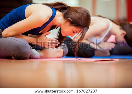 Group of young women relaxing and meditating during their yoga class in a gym - stock photo