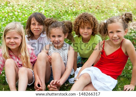 Group of youngsters sitting together in flower field. - stock photo