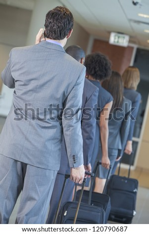 Group or team of men and women, businessmen & businesswomen talking on cell phone and traveling in line through an airport with rolling suitcases - stock photo