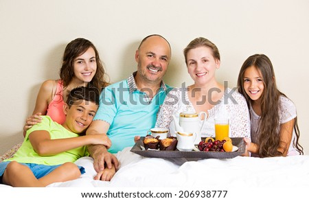Group portrait happy, smiling, joyful family, mother, father, daughters, son having breakfast in bed, surprise on mom day. Positive human emotions, face expressions, feelings, life perception  - stock photo