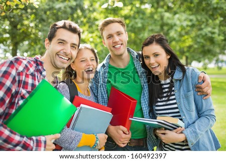 Group portrait of cheerful college students with bags and books standing in the park - stock photo