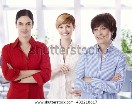 Group portrait of confident casual female caucasian business office workers. Smiling, arms crossed, looking at camera. - stock photo