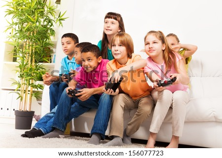 Group portrait of diversity looking children boys and girls, friends, playing videogame sitting on the couch in living room with intense expression on their faces, holding game controller  - stock photo