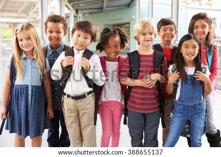 Group portrait of elementary school kids in school corridor - stock photo