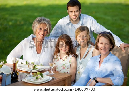 Group portrait of happy multi generation family smiling together at dining table - stock photo