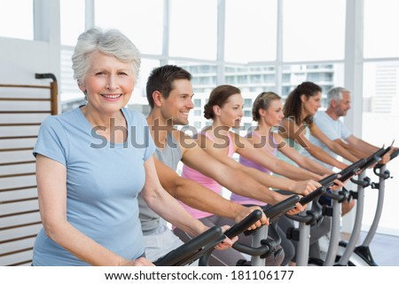 Group portrait of happy people working out at exercise bike class in gym - stock photo