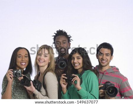 Group portrait of multiethnic young people holding cameras in studio - stock photo